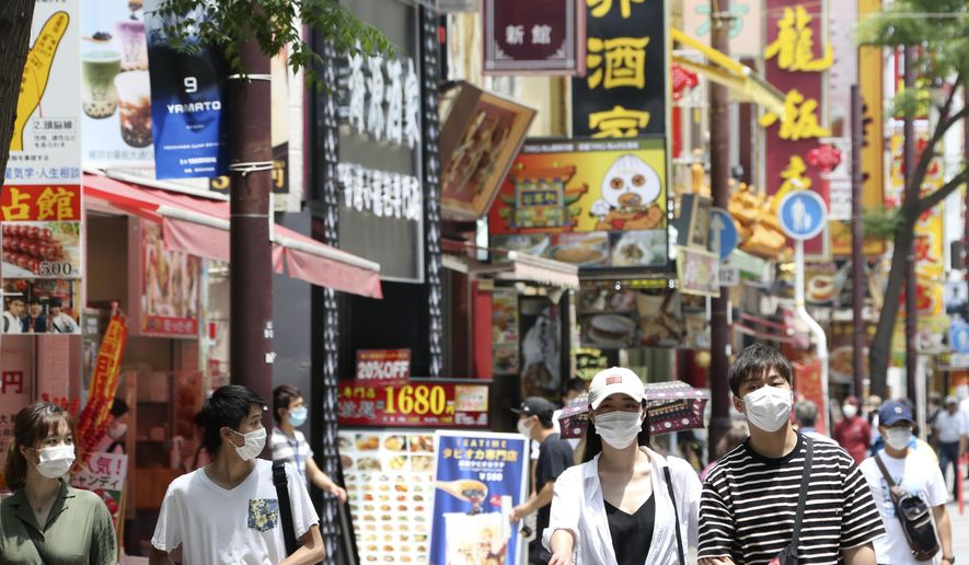 People wearing face masks to protect against the spread of the new coronavirus walk through China Town in Yokohama, near Tokyo, Wednesday, June 3, 2020. A coronavirus state of emergency was lifted, ending the restrictions nationwide as businesses began to reopen. (AP Photo/Koji Sasahara)