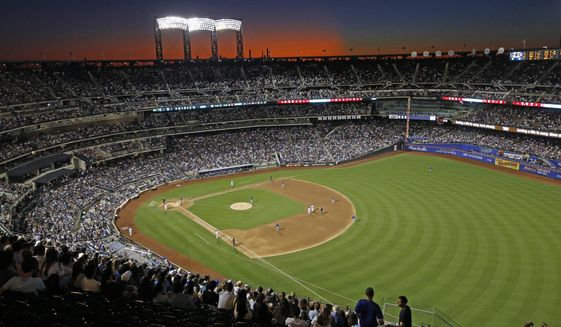 In this Aug. 29, 2019, file photo, the sun sets behind Citi Field during a baseball game between the New York Mets and the Chicago Cubs in New York. Major League Baseball players ignored claims by clubs that they need to take additional pay cuts, instead proposing they receive a far higher percentage of salaries and a commit to a longer schedule as part of a counteroffer to start the coronavirus-delayed season. (AP Photo/Kathy Willens) ** FILE **