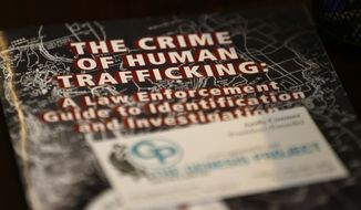 In this photo taken Feb. 27, 2017, a law enforcement guide to human trafficking sits on a table at The Genesis Project, a drop-in center for victims of sex trafficking in SeaTac, Wash. (AP Photo/Ted S. Warren) ** FILE **