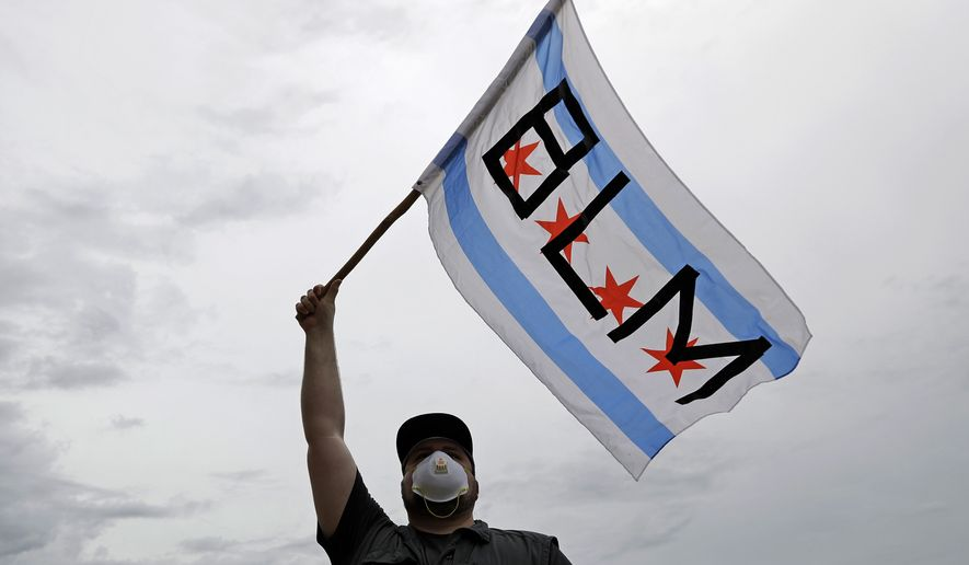 A protester waves a city of Chicago flag emblazoned with the acronym BLM for Black Lives Matter, outside the Batavia, Ill., City Hall during a protest over the death of George Floyd, on Wednesday, June 3, 2020, Floyd, an African American, died on May 25 after a white Minneapolis police officer pressed a knee into his neck for several minutes even after he stopped moving and pleading for air. (AP Photo/Nam Y. Huh)