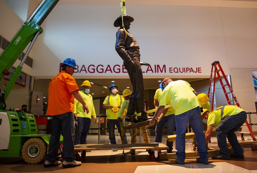 A Phoenix 1 Restoration & Construction crew removes a 12-foot-tall bronze statue of a Texas Ranger, called One Riot, One Ranger,  from the main lobby inside Love Field airport on Thursday, June 4, 2020 in Dallas. A published account of brutal and racist chapters in the history of an elite Texas investigative agency prompted Dallas officials to remove the statue from Love Fields passenger terminal that honored the agency. (Juan Figueroa/ The Dallas Morning News via AP)