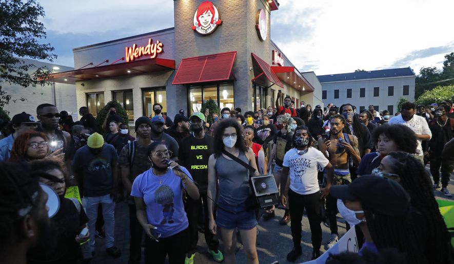 Protesters surround a Wendy's restaurant because of a franchisee's donations to President Trump as they march through the streets of New Orleans Wednesday, June 3, 2020, protesting the death of George Floyd, a black man who died in police custody in Minneapolis on May 25. (AP Photo/Gerald Herbert)
