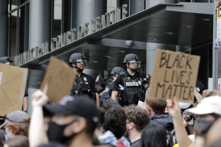 Police officers behind a barricade look on as protesters fill the street in front of the Municipal Court of Seattle, across from Seattle City Hall, Wednesday, June 3, 2020, in Seattle, following protests over the death of George Floyd, a black man who was in police custody in Minneapolis. (AP Photo/Elaine Thompson)