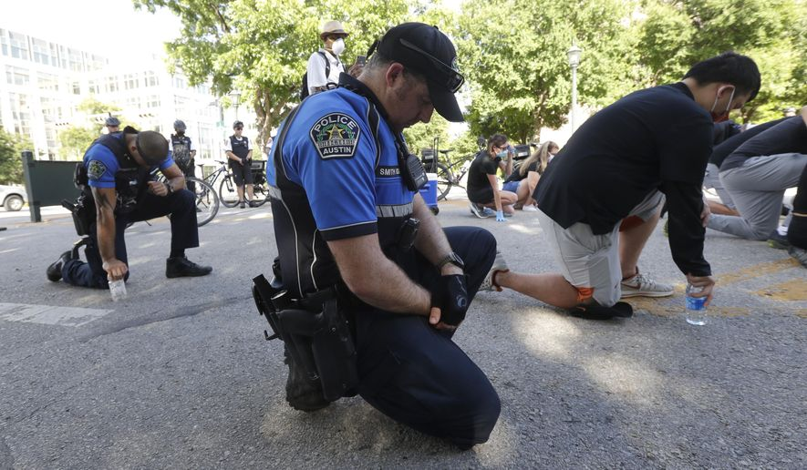 Members of the Austin police department kneel with members of the University of Texas football team, in Austin, on Thursday, June 4, 2020, after they marched to the State Capitol to protest the death of George Floyd, an African American man who died on May 25 after a white Minneapolis police officer pressed a knee into his neck for several minutes even after he stopped moving and pleading for air. (AP Photo/Eric Gay)