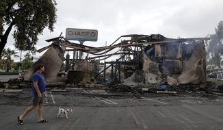 A man passes a bank burned during a protest over the death of George Floyd, Sunday, May 31, 2020, in La Mesa, Calif. A widely-seen video of a white police officer pushing the black man was taken after the officer stopped him for smoking on a trolley platform, authorities said Wednesday, providing additional details on what led to widespread damage during a protest days later. (AP Photo/Gregory Bull)