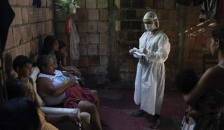 A health worker give instructions to members of Da Costa family after some of them tested positive for COVID-19 at their home in Manacapuru, Amazonas state, Brazil, Wednesday, June 3, 2020. (AP Photo/Felipe Dana)