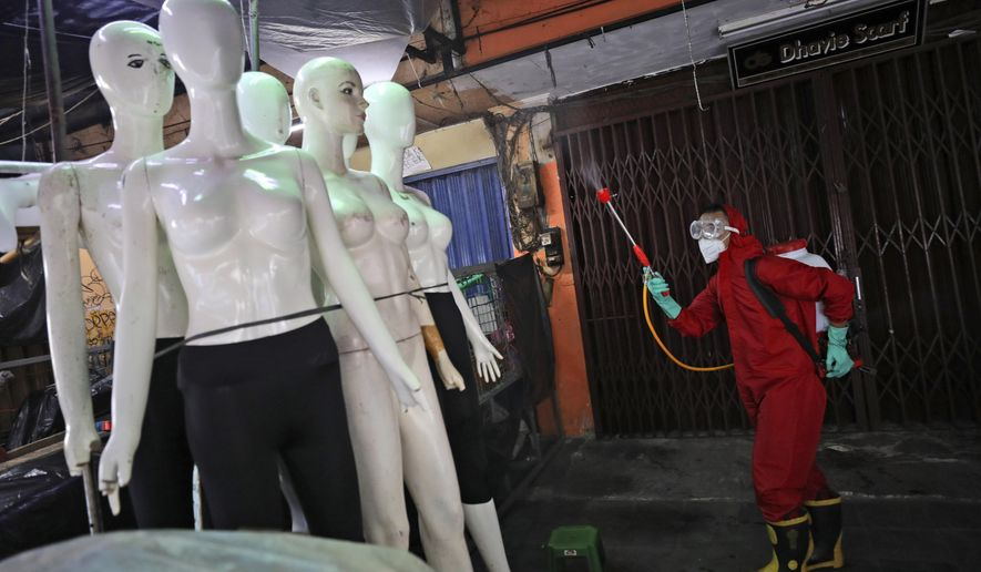 A fireman sprays disinfectant at mannequins as a precaution against coronavirus outbreak, at Tanah Abang textile market in Jakarta, Indonesia, Thursday, June 4, 2020. Authorities in Indonesia's capital will ease a partial lockdown as the world's fourth most populous nation braces to gradually reopen its economy. (AP Photo/Dita Alangkara)