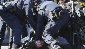 San Jose police subdue a man prior to arresting him during a protest over the Memorial Day death of George Floyd, a handcuffed black man in police custody in Minneapolis, Friday, May 29, 2020, in San Jose, Calif. (AP Photo/Ben Margot)