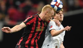 """FILE - In this Oct. 19, 2019, file photo, Atlanta United defender Jeff Larentowicz, left, and New England Revolution midfielder Scott Caldwell battle for a header during round one of an MLS Cup playoff soccer game in Atlanta. Atlanta United veteran defender Jeff Larentowicz, who serves as an executive board member for the players union, said Thursday, June 4, 2020, he has safety concerns about an agreement announced Wednesday for a MLS tournament in Orlando in July. He is worried about the ongoing coronavirus pandemic and said """"We play a contact sport and the virus is a serious thing that puts us all in danger."""" (AP Photo/John Amis, File)"""