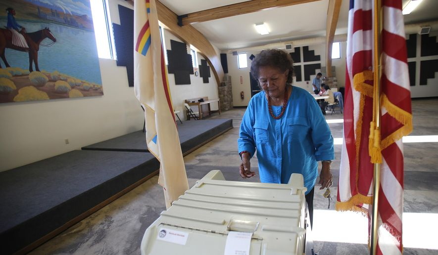 FILE - In this July 21, 2015, file photo, Martha Johnson turns in her ballot at the Nenahnezad Chapter House in Fruitland, N.M., during the Navajo Nation's referendum election. Native American voting rights advocates are cautioning against states moving to mail-in ballots without opportunities for tribal members to vote safely in person. The Native American Rights Fund released a wide-ranging report on voting rights Thursday, June 4, 2020. In it, the group outlined the challenges that could arise as states move to rely more heavily on mail-in ballots. (Jon Austria/The Daily Times via AP, File)