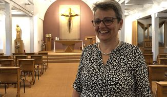 Marianne Pohl Henzen smiles in the Saint Paul sisters church in Fribourg, Switzerland, Wednesday, June 3, 2020. A Swiss bishop's appointment of Marianne Pohl Henzen, a lay mother of three, to a senior administrative post previously held by a priest has raised eyebrows in conservative Catholic circles, at a time when a strengthened role for women in the church is under debate in other European countries. (AP Photo/Nadine Achoui-Lesage)