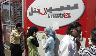 FILE - In this July 25, 2006, file photo, Lebanese refugees at the Syrian-Lebanese border crossing at Jdaidet Yabous talk with their relatives in Lebanon through mobile phones provided free by Syrian telecommunication company Syriatel. The unprecedented public crackdown on Syria's wealthiest businessman Rami Makhlouf, a close cousin of Bashar Assad, comes as the embattled president seeks to consolidate power and rein in war profiteers. Syria is preparing for a new phase of economic hardship and U.S.-led sanctions that some say might be more difficult to weather than war. (AP Photo/ Bassem Tellawi, File)