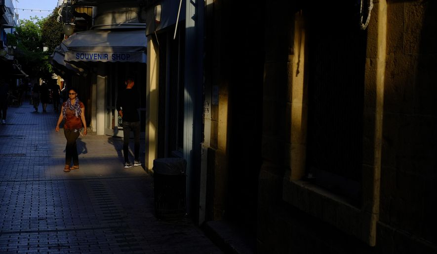 A woman walks past a closed souvenir shop in central capital Nicosia, Cyprus, Wednesday, June 3, 2020. Health Minister Constantinos Ioannou said the third phase of the country's gradual rollback of restrictions will be completed by June 24 instead of July 14. (AP Photo/Petros Karadjias)