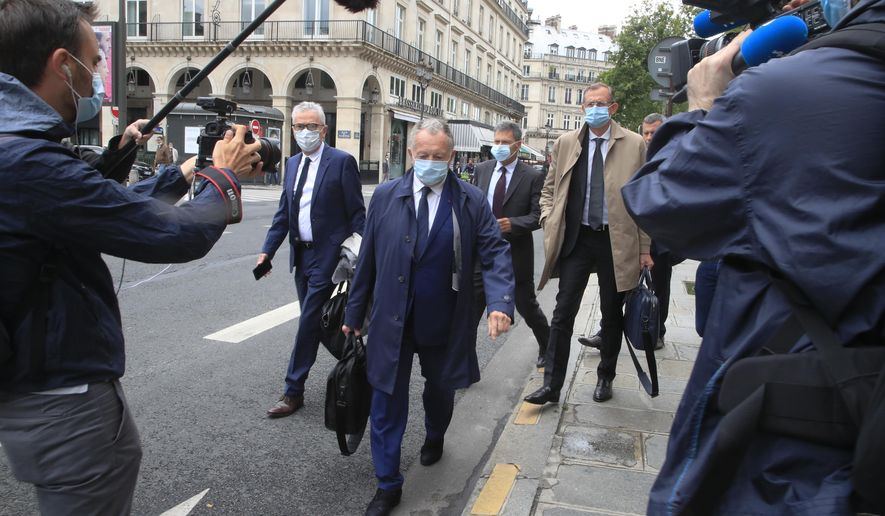 Lyon soccer club President Jean-Michel Aulas, center, wears a mask as he arrives with his legal team for a hearing at France's highest administrative court, the Council of State, in Paris, Thursday, June 4, 2020. Jean-Michel Aulas is asking French authorities to backpedal on their decision to end the football season prematurely amid the coronavirus pandemic. The men's league was canceled with 10 rounds remaining, Paris Saint-Germain declared champion, and Lyon finished outside the European places in seventh. (AP Photo/Michel Euler)