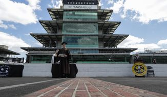 Eli Collins receives his Speedway High School diploma during a ceremony on the start/finish line at the Indianapolis Motor Speedway in Indianapolis, Saturday, May 30, 2020. The ceremony was held at the track to allow for social distancing requirements due to the COVID-19 pandemic. (AP Photo/Michael Conroy)