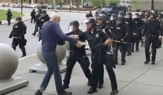 In this image from video provided by WBFO, a Buffalo police officer appears to shove a man who walked up to police Thursday, June 4, 2020, in Buffalo, N.Y. The officer and another involved in the incident have been charged with second-degree assault.  (Mike Desmond/WBFO via AP)