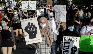 Amena Shukairy, 19, center front, of Flushing, Mich., holds a black lives matter sign as she marches north on Saginaw Street with other people peacefully protesting against police violence and racial injustice on Friday, June 5, 2020 in Grand Blanc, Mich. Protests continued Friday across the United States and elsewhere in the wake of the death of George Floyd who died after being restrained by Minneapolis police officers on May 25. (Jake May/The Flint Journal via AP)