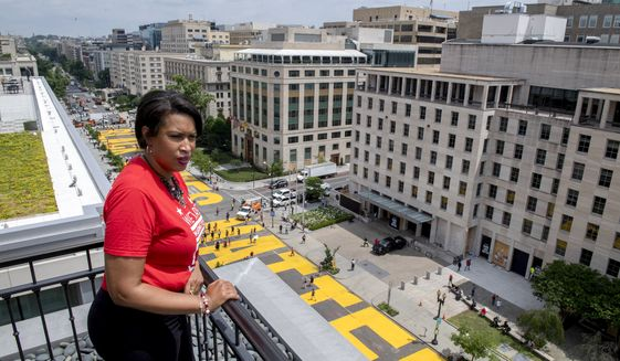 In this image provided by the Executive Office of the Mayor, District of Columbia Mayor Muriel Bowser stands on the rooftop of the Hay Adams Hotel near the White House and looks out at the words 'Black Lives Matter' that have been painted in bright yellow letters on the street by city workers and activists, Friday, June 5, 2020, in Washington. (Executive Office of the Mayor/Khalid Naji-Allah via AP) ** FILE **