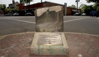 This May 5, 2005, file photo, shows the historic pre-civil war auction block for slaves and property at the corner of Charles and William Streets in downtown Fredericksburg, Va. The 800-pound stone was pulled from the ground at a Fredericksburg street corner early Friday, June 5, 2020, after its removal was delayed for months by lawsuits and the coronavirus pandemic, The Free Lance-Star reported. (Reza A Marvashti/The Free Lance-Star via AP, File)