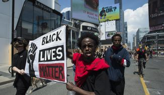 People hold up a Black Lives Matter sign as thousands of people protest at an anti-racism demonstration, in Toronto on Friday, June 5, 2020. George Floyd, a black man, died after he was restrained by Minneapolis police officers on May 25. His death has ignited protests in the U.S. and worldwide over racial injustice and police brutality. (Nathan Denette/The Canadian Press via AP)