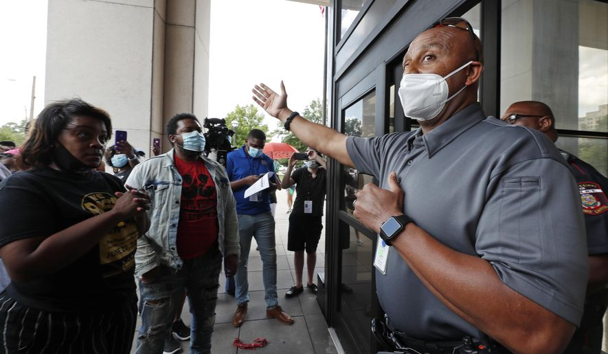 A Capitol police official explains the Walter Sillers State Office Building is closed to the public due to the coronavirus pandemic during a protest Friday, June 5, 2020, in Jackson, Miss., over Mississippi Attorney General Lynn Fitch's recent decision to drop a manslaughter charge against former Columbus Police Officer Canyon Boykin. Boykin, who is white, had been charged in the October 2015 shooting death of an African American man, Ricky Ball. Ball's family intended to deliver a letter to Fitch asking her to reopen the case but Capitol Police refused entry to the building. (AP Photo/Rogelio V. Solis)