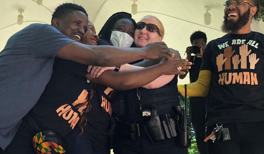 """Sgt. Cristie Jacobsen, center, of the Fargo Police Department, receives hugs from organizers at the end of a George Floyd memorial in Fargo, N.D., Friday, June 5, 2020. Jacobson was brought up to the stage at Island Park while musicians performed the song """"Lean on Me."""" Hundreds of people attended the peaceful rally that included speeches, live music and dancing. (AP Photo/Dave Kolpack)"""