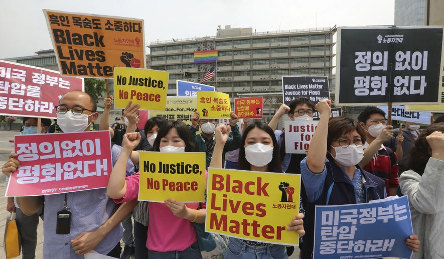 """South Korean protesters shout slogans during a protest over the death of George Floyd, a black man who died after being restrained by Minneapolis police officers on May 25, near the U.S. embassy in Seoul, South Korea, Friday, June 5, 2020. The signs read """"The U.S. government should stop oppression and there is no peace without justice."""" (AP Photo/Ahn Young-joon)"""
