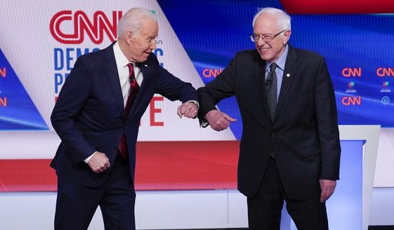 FILE - In this March 15, 2020, file photo, former Vice President Joe Biden, left, and Sen. Bernie Sanders, I-Vt., right, greet one another before they participate in a Democratic presidential primary debate at CNN Studios in Washington. Biden has won the last few delegates he needed to clinch the Democratic nomination for president. (AP Photo/Evan Vucci, File)