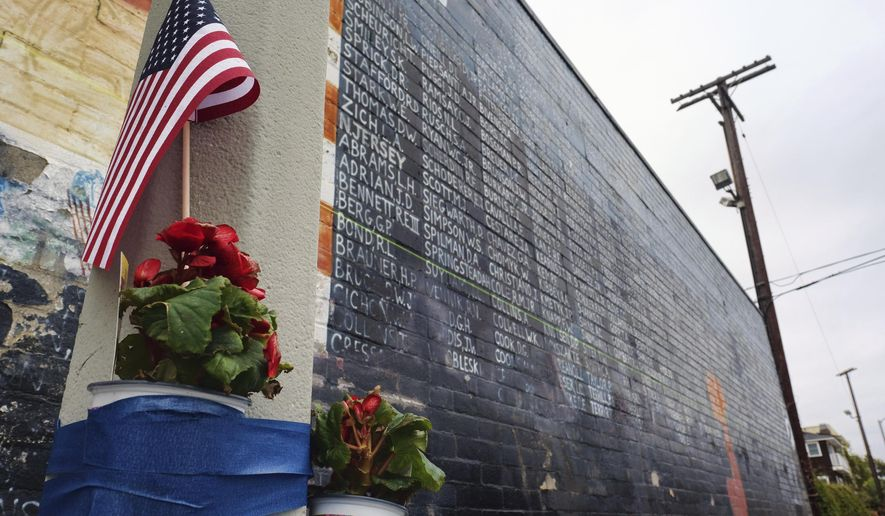 FILE - This Monday, May 30, 2016 file photo shows flowers left next to a vandalized Vietnam War memorial in the Venice area of Los Angeles. On Friday, June 5, 2020, The Associated Press reported on stories photos online incorrectly identified as the Vietnam Veterans Memorial in Washington marred by graffiti as a result of riots after the death of George Floyd. The photos circulating on social media are from 2016 and show this Vietnam Veterans Memorial replica in Los Angeles, which was defaced in that year. (AP Photo/Richard Vogel, File)