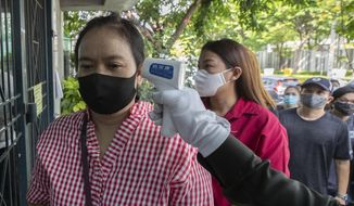 An officer checks the temperature ofWannapa Kotabin, a 38-year-old kitchen assistant at an Italian restaurant, in front of Social Security office for claim unemployment benefit in Bangkok, Thailand, Thursday, June 4, 2020. The government ordered all restaurants closed in March to combat the spread of the coronavirus, and Wannapa hasn't worked since. That's the harsh truth facing workers laid off around the world, from software companies in Israel to restaurants in Thailand and car factories in France, whose livelihoods fell victim to a virus-driven recession that's accelerating decline in struggling industries and upheaval across the global workforce. (AP Photo/Sakchai Lalit)