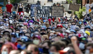 Protesters holds up signs as the group sits down in the intersection of Penn Ave and Bakery Square, Saturday, June 6, 2020, during a Black Lives Matter rally in Pittsburgh to protest the death of George Floyd, who died after being restrained by Minneapolis police officers on May 25. (AP Photo/Keith Srakocic)