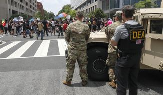 As a Drug Enforcement Agency police office and National Guard soldiers watch, demonstrators protest Saturday, June 6, 2020, in Washington, over the death of George Floyd, a black man who was in police custody in Minneapolis. Floyd died after being restrained by Minneapolis police officers. (AP Photo/Alex Brandon)
