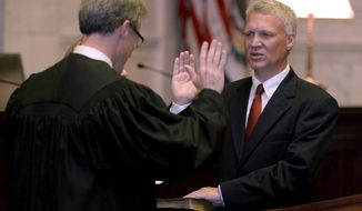 FILE - In this Sept. 25, 2018 file photo, Tim Armstead, right, former speaker of the West Virginia House of Delegates, is sworn in as a state Supreme Court justice by his former House chief of staff, Kanawha Circuit Judge Dan Greear, in the court's chamber at the Capitol in Charleston, W.Va.  Armstead is running for a Supreme Court seat on Tuesday, June 9, 2020. (Chris Dorst/Charleston Gazette-Mail via AP)