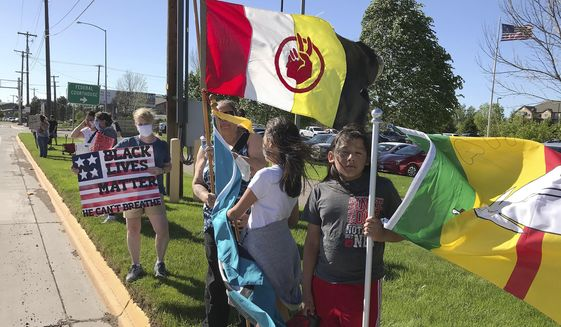 In this May 30, 2020 photo, Debbie McShane stands with her children, Kendalyn and Sky Running Enemy in Great Falls, Mont., at a rally for George Floyd, who died May 25 after being restrained by Minneapolis. Tribal members in Montana are wondering if they will be included in the dialogue about changing race relations. (Karl Puckett/The Great Falls Tribune via AP)