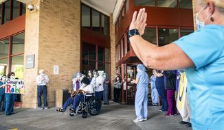 Robin Eaton is cheered by staff at Novant Health Forsyth Medical Center as she leaves the hospital after recovering from COVID-19 on Thursday, June 4, 2020 in Winston-Salem, N.C. . Robin Eaton, who works at Forsyth Medical Center as a patient sitter, was the 1,000th COVID-19 patient successfully treated within the Novant Health system in North Carolina and Virginia, said Josh Jarman, a spokesman for the Novant Health.(Andrew Dye/The Winston-Salem Journal via AP)