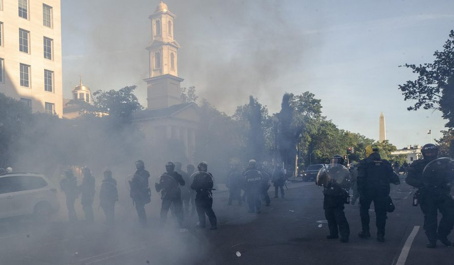 In this June 1, 2020, file photo police move demonstrators away from St. John's Church across Lafayette Park from the White House, as they gather to protest the death of George Floyd in Washington. Floyd died after being restrained by Minneapolis police officers. (AP Photo/Alex Brandon, File)