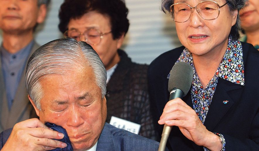 Shigeru Yokota, bottom left, wipes tears as he and his wife Sakie, right, speak during a press conference in Tokyo in September, 2002 after they were informed that their daughter Megumi, abducted to North Korea in the 1970s, had died. Shigeru Yokota died of natural causes before he was able to meet his daughter again, his group said Friday, June 5, 2020. He was 87. (Kyodo News via AP)