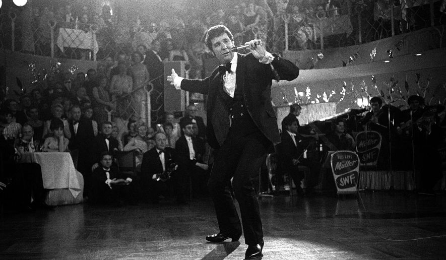 """FILE - In this Dec. 31, 1968 file photo, Tom Jones performs at the """"Bal Pare"""" in Munich, Germany. Jones, the Welsh star whose snake hips and stage presence earned comparisons to Elvis Presley, turns 80 on Sunday, June 7. (AP Photo, File)"""