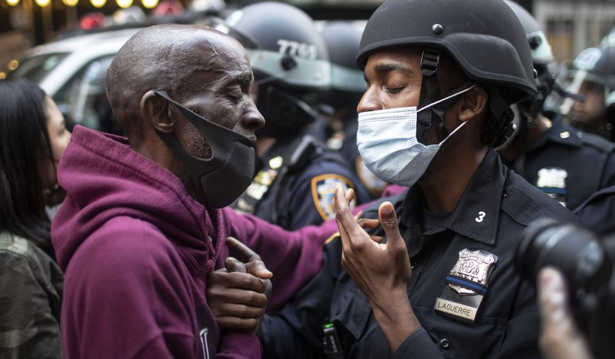 A protester and a police officer hold hands in the middle of a standoff during a solidarity rally calling for justice over the death of George Floyd in New York, on Tuesday, June 2, 2020. Floyd died after being restrained by Minneapolis police officers on May 25. (AP Photo/Wong Maye-E)