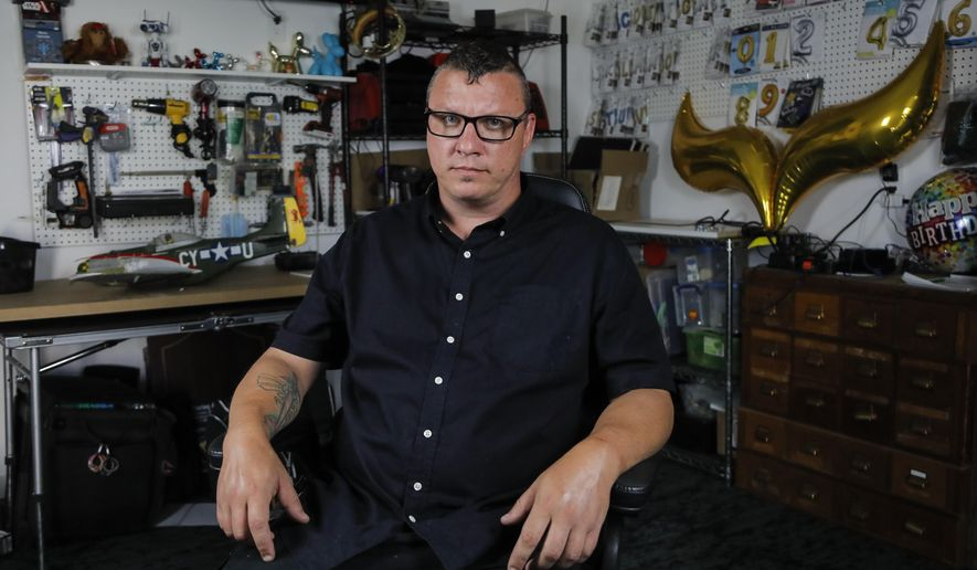 In a photo taken Friday, June 5, 2020, Scott Nichols, aka Amazing Scott, a local balloon artist, poses for The Associated Press in his balloon shop in Minneapolis. Nichols doesn't consider himself very political, but when George Floyd died, he felt compelled to join the protests which happened to be a few blocks from his home. He was arrested during one of the protests and spent 48 hours in jail before he was released. (AP Photo/Julio Cortez)
