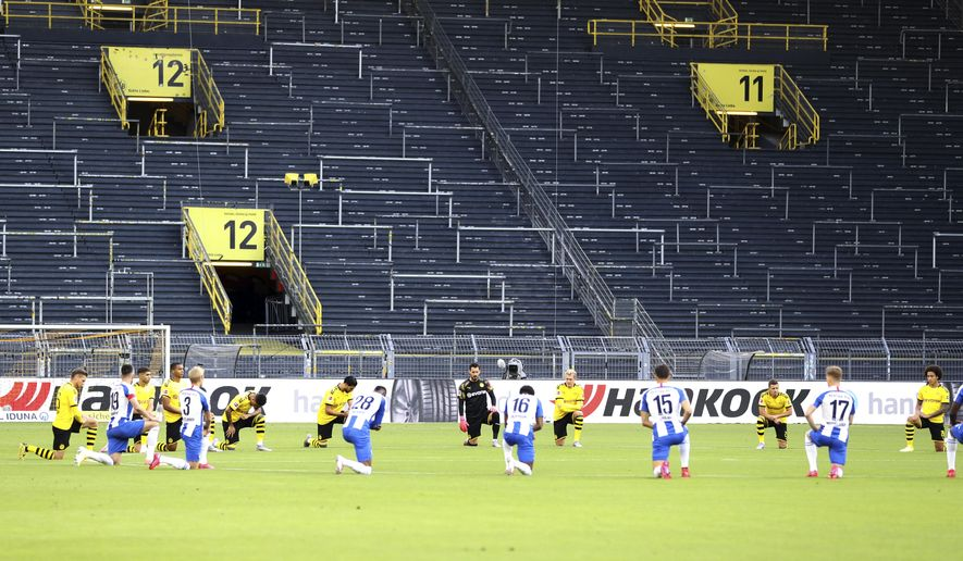 Players of both teams (Dortmund yellow jersey) kneel around the centre circle as a mark of support for the protests after the recent killing of black American George Floyd by police officers in Minneapolis, USA, before the German Bundesliga soccer match between Borussia Dortmund and Hertha BSC Berlin in Dortmund , Germany, Saturday, June 6, 2020. (Lars Baron, Pool via AP)