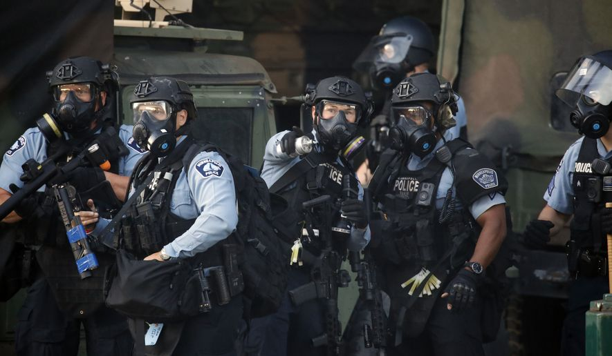 Police prepare to engage protesters Friday, May 29, 2020, in Minneapolis. Protests continued following the death of George Floyd who died after being restrained by Minneapolis police officers on Memorial Day. (AP Photo/John Minchillo)