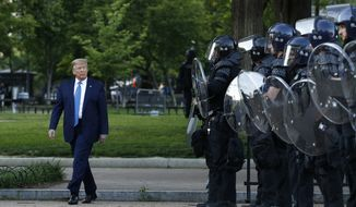 In this Monday, June 1, 2020, file photo President Donald Trump walks past police in Lafayette Park after visiting outside St. John's Church across from the White House in Washington. (AP Photo/Patrick Semansky, File)