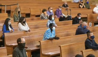 Congregants kneel and observe social distancing while listening to Los Angeles Archbishop Jose H. Gomez celebrate Mass at Cathedral of Our Lady of the Angels in downtown Los Angeles, Sunday, June 7, 2020. (AP Photo/Damian Dovarganes) ** FILE **