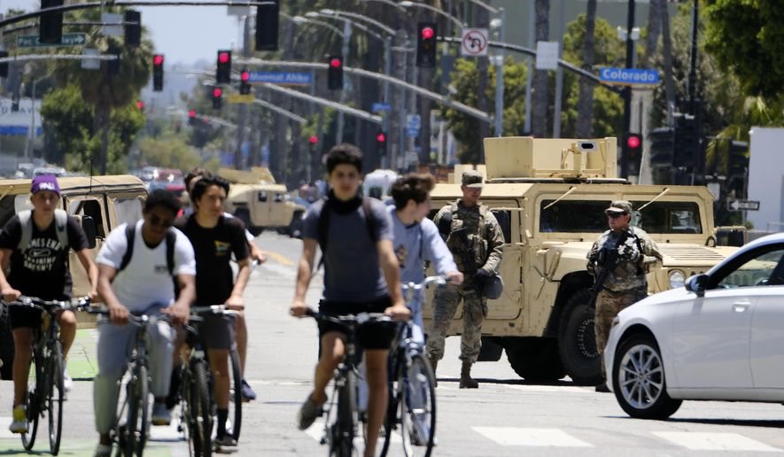 Cyclists ride down a street past a road block with National Guard troops along Ocean boulevard in Santa Monica, Calif. on Sunday June 7,2020.  Officials announced Sunday that National Guard troops will be pulled out of California cities where they've been deployed for a week after rampant violence and thievery marred the first days of protests over the death of George Floyd. (AP Photo/Richard Vogel)