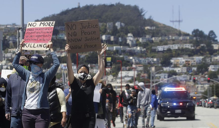 People carry signs while marching in San Francisco, Sunday, June 7, 2020, during a protest over the death of George Floyd, who died May 25 after being restrained by police in Minneapolis. (AP Photo/Jeff Chiu)