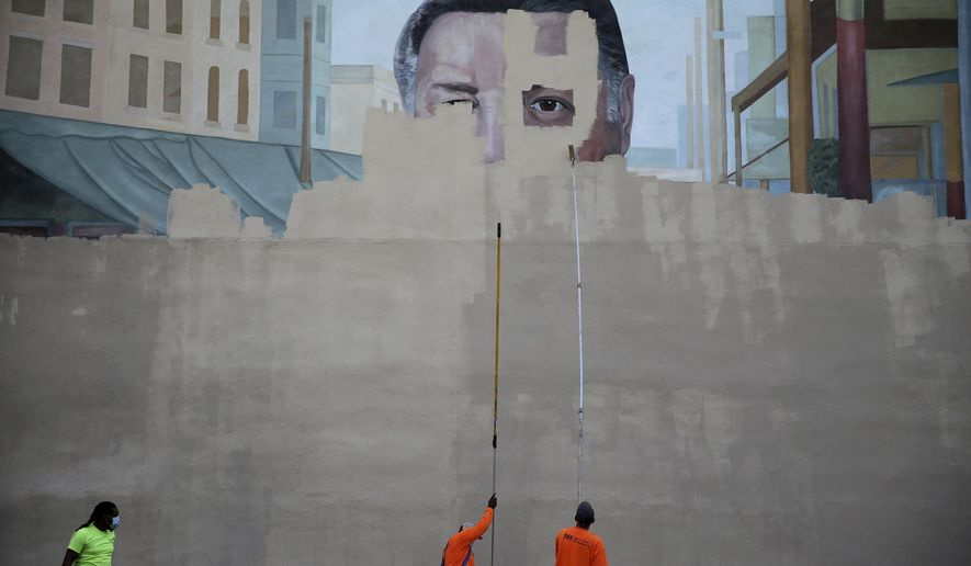 A crew from Mural Arts paints over the Frank Rizzo mural on 9th Street in Philadelphia, on Sunday, June 7, 2020. The image of the former Philadelphia mayor was removed from the side of a building in south Philadelphia amid large protests in the city on the issue of police brutality.  (David Maialetti/The Philadelphia Inquirer via AP)