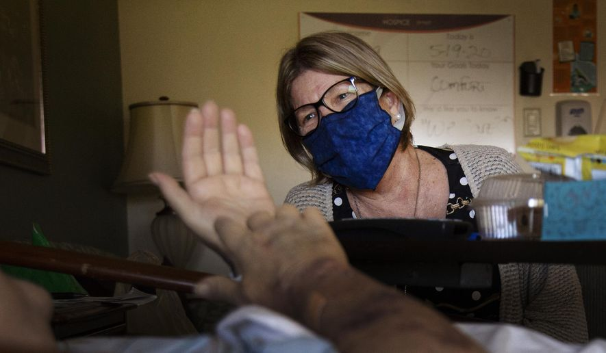 Suncoast Hospice Spiritual Care Coordinator Victoria Long talks with a hospice resident Tuesday, May 19, 2020 in St. Petersburg, Fla. (John Pendygraft/Tampa Bay Times via AP)