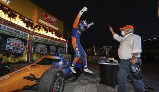 In this photo provided by Chris Owens/INDYCAR Series, Scott Dixon, left, jumps off his car toward team owner Chip Ganassi as the two celebrate Dixon's IndyCar auto race win at Texas Motor Speedway in Fort Worth, Texas, Saturday, June 6, 2020. (Chris Owens/INDYCAR Series via AP)  **FILE**