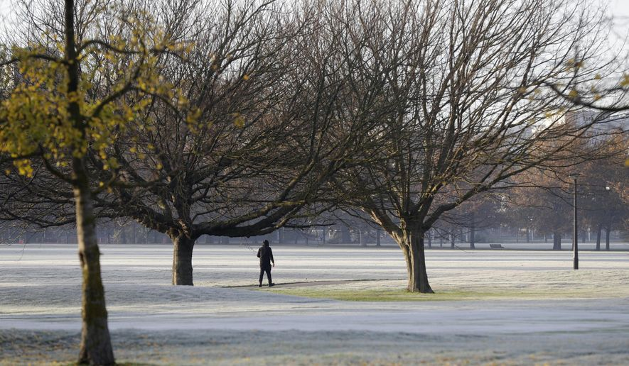 A man walks across the frost covered fairways of a golf course in central Christchurch, New Zealand, Saturday, June 6, 2020. (AP Photo/Mark Baker)